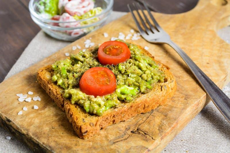 鲕梨多士用全麦面包和菜沙拉 免版税库存图片