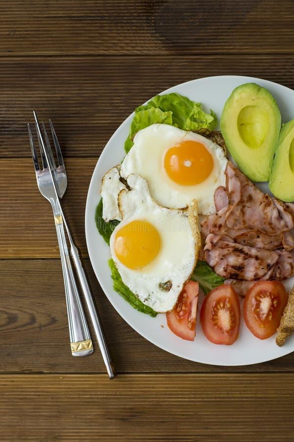 鲕梨早餐,荷包蛋用在木背景的整个五谷多士面包 垂直的图象,顶视图 免版税库存图片