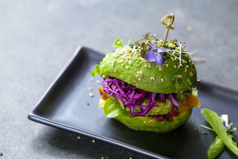 鲕梨汉堡用绿色小馅饼 库存照片
