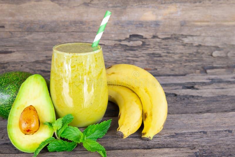 鲕梨混合香蕉圆滑的人和绿色汁液喝在一块玻璃的健康,可口口味减重的 图库摄影