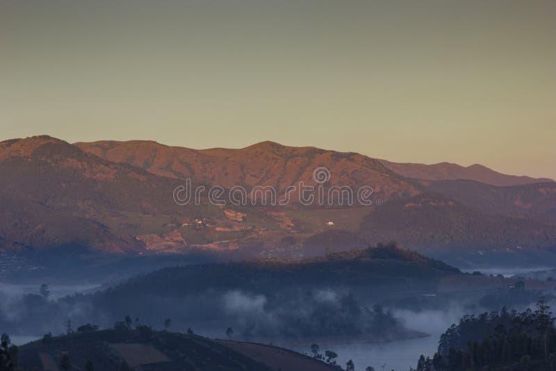 鲜绿色与落在西部ghats山的金黄太阳光的湖有薄雾的清早视图在湖后 库存图片