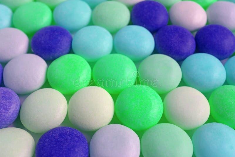 鲜绿色和蓝色色的圆的形状的糖果行  库存照片