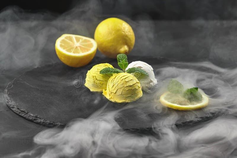 鲜美乳脂状和柑橘柠檬冰淇淋装饰用在黑背景的石板岩供食的薄菏 库存照片