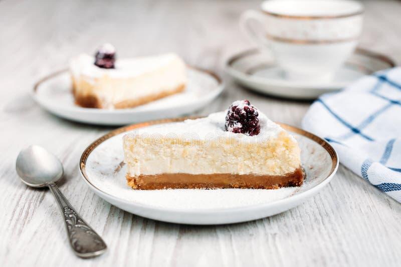 鲜美乳酪蛋糕用在放置在与另一杯蛋糕和咖啡的一张白色木桌的板材的黑莓或茶在backgroun 免版税图库摄影