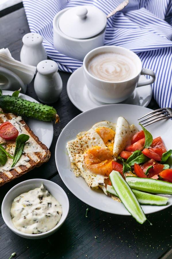鲜美和健康早餐荷包蛋、菜沙拉、多士与奶油奶酪和芝麻菜和热奶咖啡在黑暗的背景 免版税库存图片