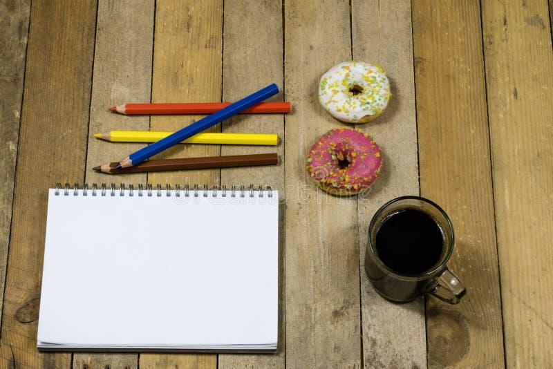 鲜美和新鲜的油炸圈饼和笔记本,画的铅笔 Sket 免版税库存照片