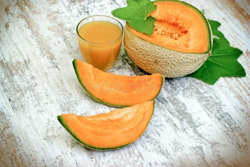 鲜美和水多的瓜-甜瓜和瓜在土气桌上的汁圆滑的人 免版税库存照片
