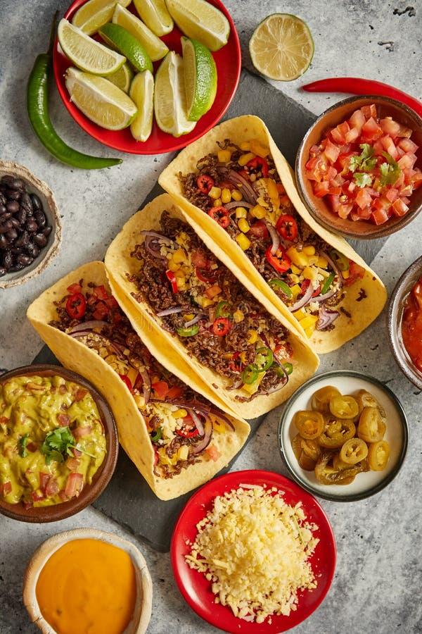 鲜美墨西哥肉炸玉米饼服务与各种各样的菜和辣调味汁 库存照片