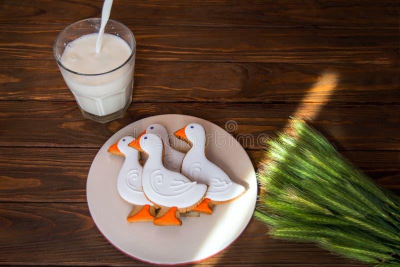 鲜美姜饼吮在一块板材的形状的曲奇饼有杯的牛奶和有麦子的耳朵的在木背景的 免版税库存照片