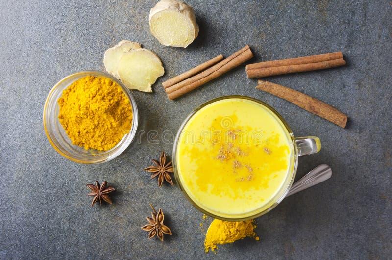 鲜美姜黄拿铁顶视图在土气桌上的 各种各样spiece和杯子新鲜和热的金黄牛奶 匙子和碗与 免版税库存图片