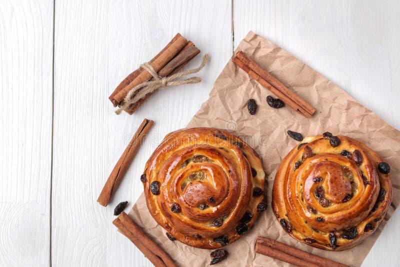 鲜美小圆面包用葡萄干和桂香在白色木背景 新鲜的面包店 早餐视图从上面 库存照片