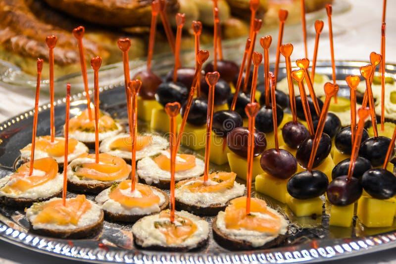 鲜美开胃菜用乳酪和鱼和葡萄和乳酪在银色盛肉盘 免版税库存图片