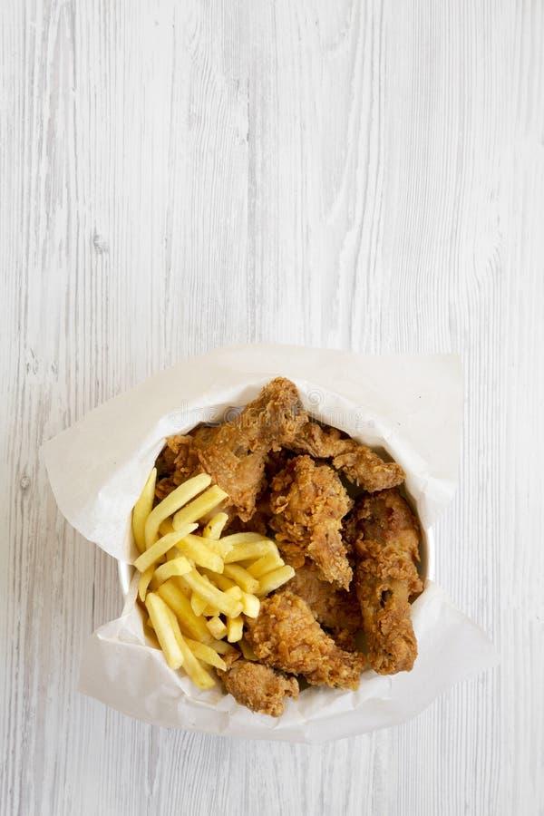 鲜美快餐:炸鸡鼓槌、辣翼、炸薯条和招标小条在纸箱在白色木背景, 图库摄影