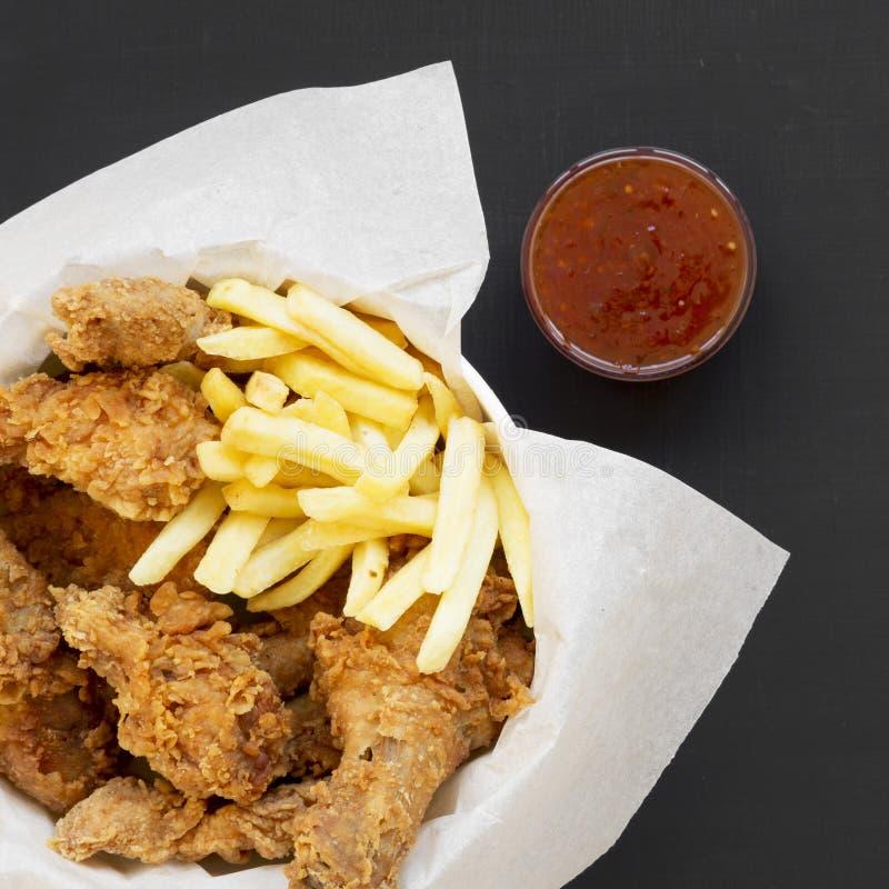 鲜美快餐:炸鸡鼓槌、辣翼、薯条和鸡小条在一个纸箱,酸甜调味汁在黑色 免版税库存照片