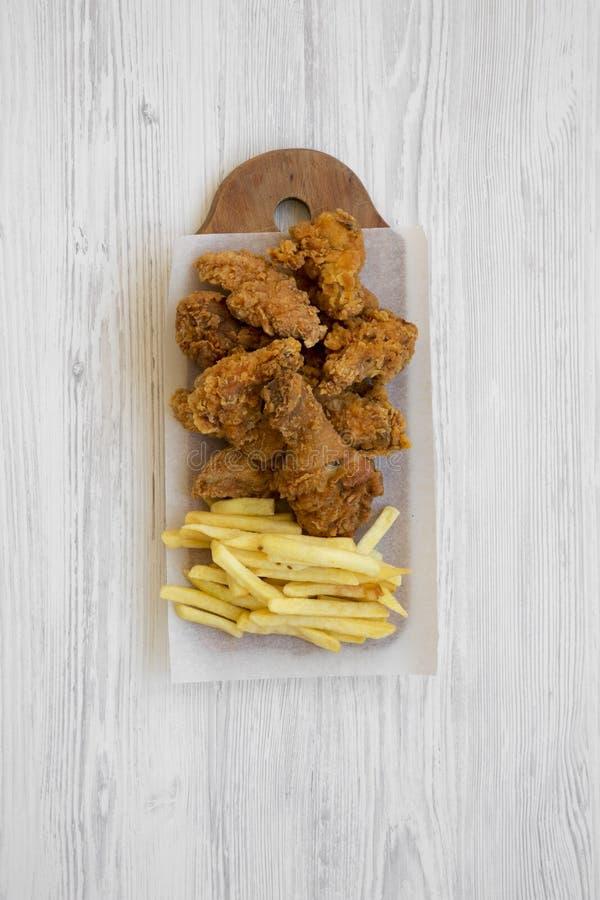 鲜美快餐:炸鸡鼓槌、辣翼、薯条和鸡小条在土气木板在白色木 免版税库存图片