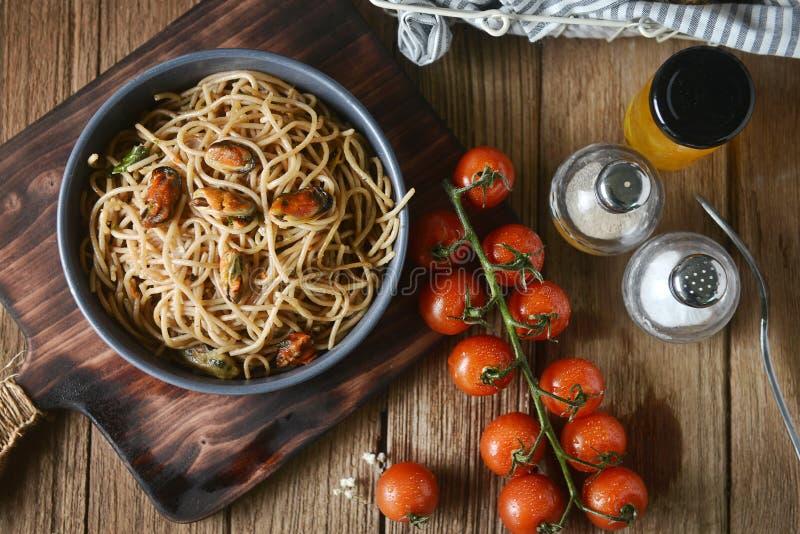 鲜美意大利意粉面团用淡菜、蕃茄和装饰品在圆的盘和木板材服务的在木桌上 免版税库存照片