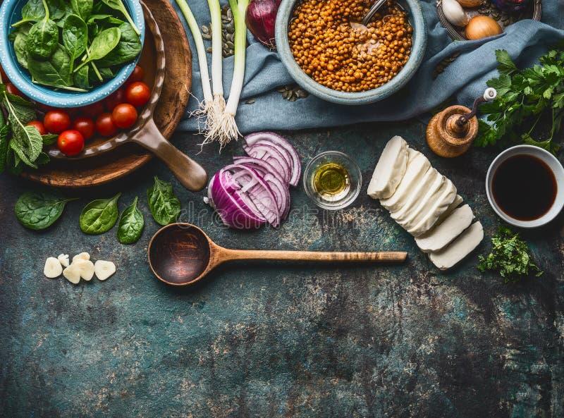 鲜美扁豆盘的素食成份在与烹调匙子和器物,顶视图, borde的土气厨房用桌背景 免版税库存照片
