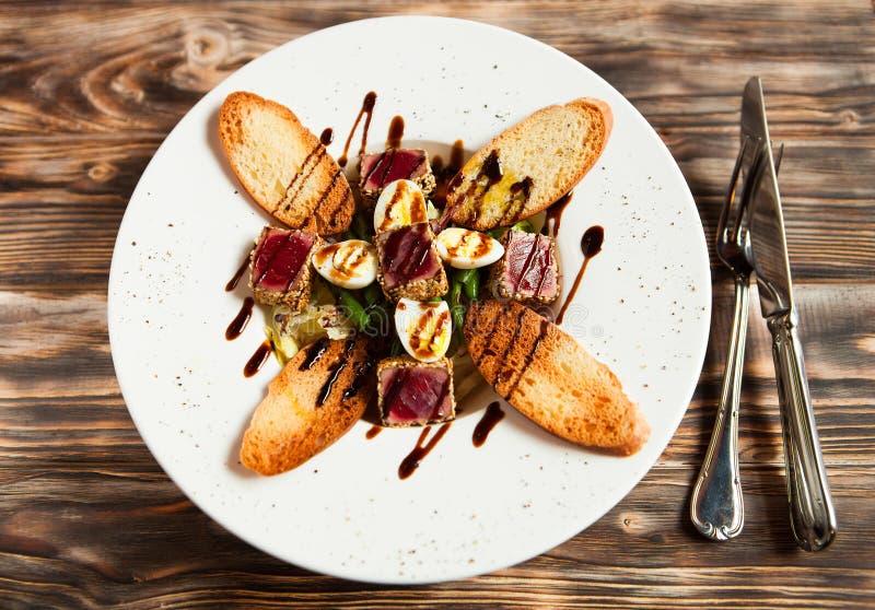 鲜美新鲜的肉、鹌鹑蛋、油煎方型小面包片和菜沙拉 免版税库存照片