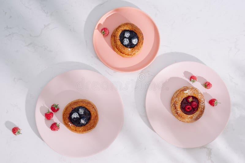 鲜美新鲜的自创油酥点心用在白色木桌上的莓果 免版税库存照片