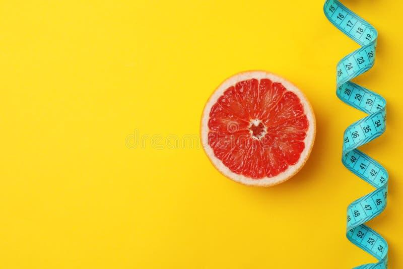 鲜美新鲜的葡萄柚和测量的磁带 免版税库存图片