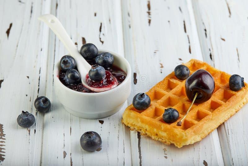 鲜美早餐比利时华夫饼干用被鞭打的奶油色蓝莓和果酱在木白色 免版税图库摄影
