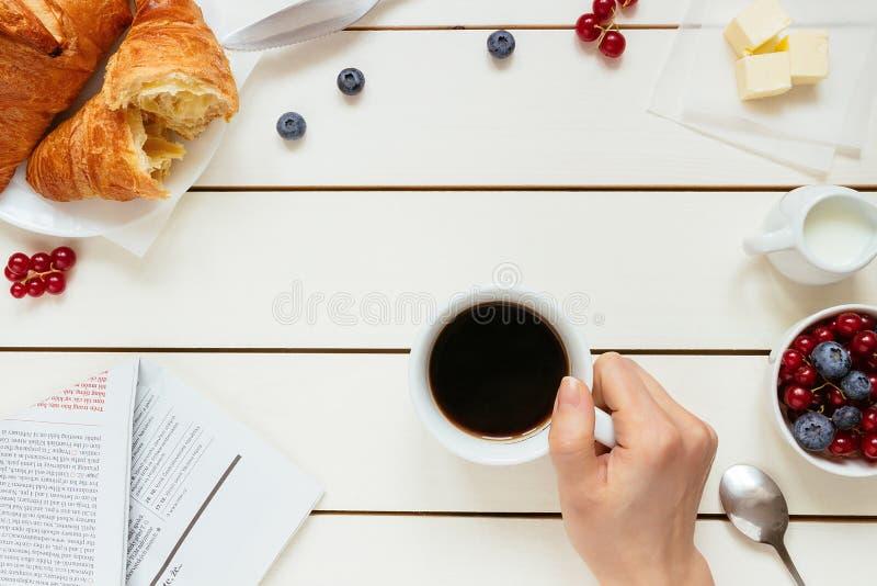 鲜美早餐用咖啡,莓果,在白色木桌上的新月形面包与拷贝空间,顶视图 免版税库存照片