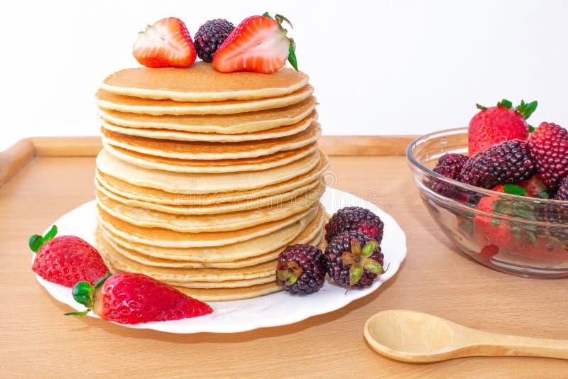 鲜美早餐薄煎饼用果子,草莓和黑莓mora,倾倒了在一个木盘子之上的糖浆蜂蜜 库存照片