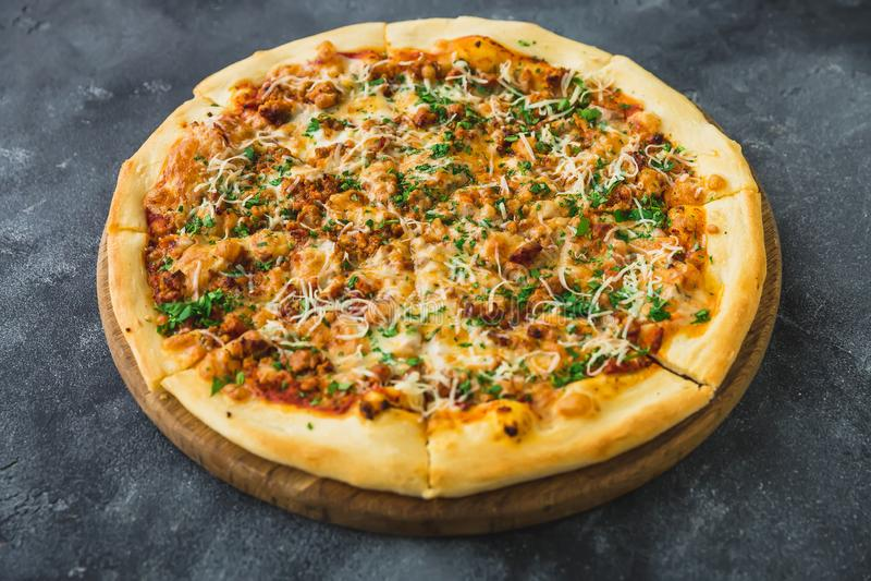 鲜美比萨特写镜头视图用烟肉、乳酪和蕃茄在黑暗的桌上 免版税库存照片