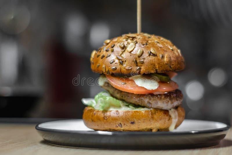 鲜美汉堡用烤牛肉、在规则明亮的厨房,关闭的陶瓷板材供食的莴苣和蛋黄酱,与 免版税库存图片