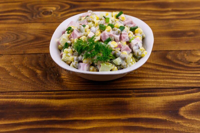 鲜美沙拉用香肠、绿豆、罐装玉米、甜椒、黄瓜和蛋黄酱在木桌上 免版税库存照片