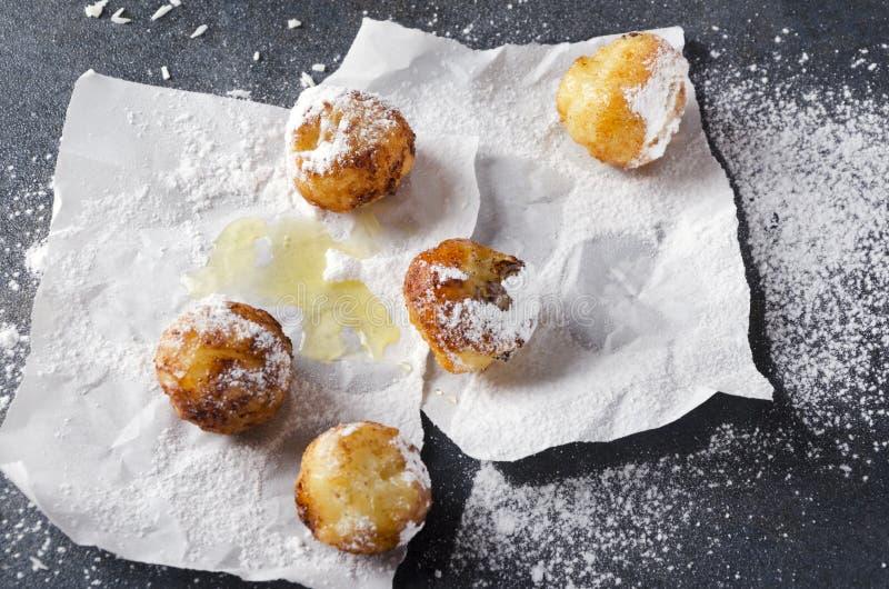 鲜美油煎的面团球用乳酪和糖粉在烘烤的纸,灰色土气表面 免版税库存图片