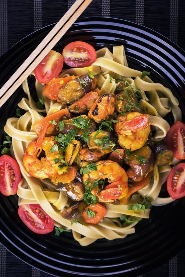 鲜美泰国面条用虾和海鲜和菜在黑盘 顶视图 免版税图库摄影