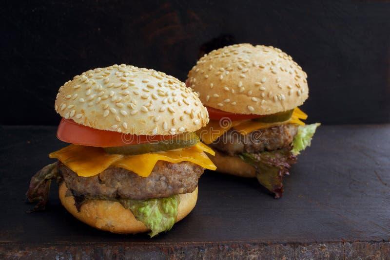 鲜美烤可口汉堡用莴苣、乳酪、葱和蕃茄在一个土气木板条 库存照片