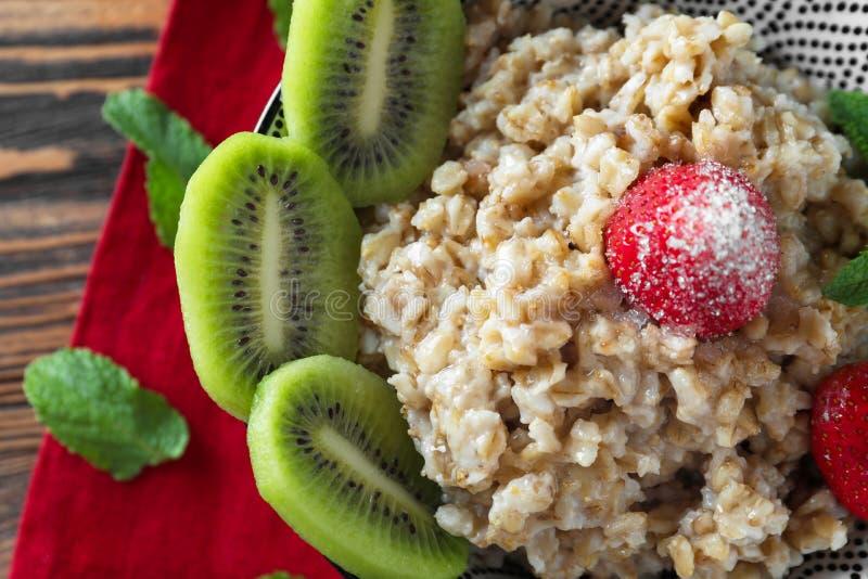鲜美燕麦粥用新鲜的草莓和被切的猕猴桃在桌,特写镜头上 免版税图库摄影