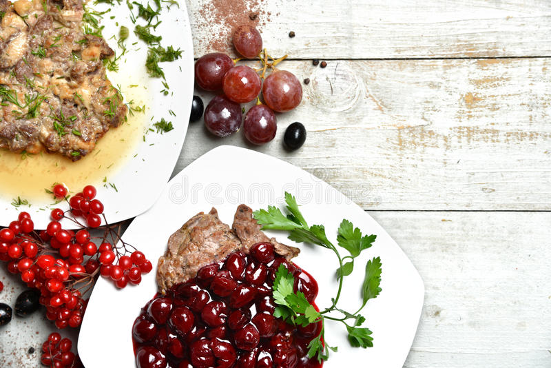 鲜美牛肉和猪肉盘装饰用樱桃和葡萄 库存图片