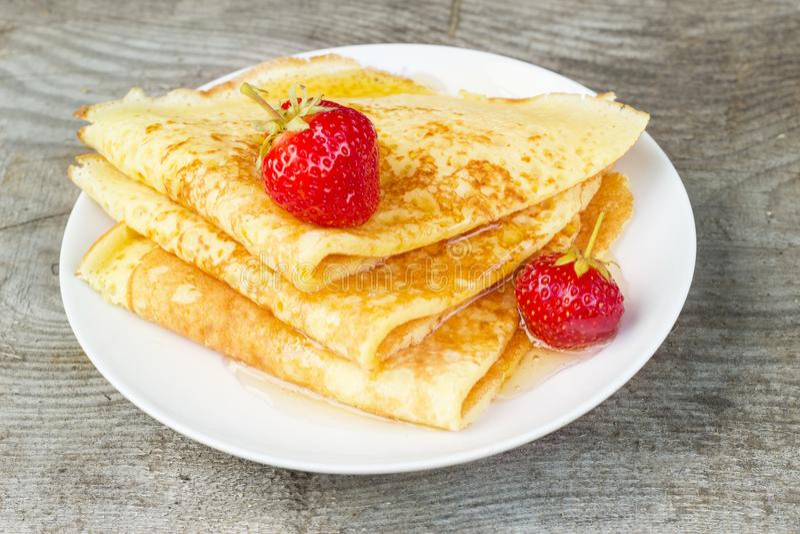 鲜美甜稀薄的薄煎饼用新鲜的草莓和蜂蜜在板材,可口点心,特写镜头,木背景 库存照片