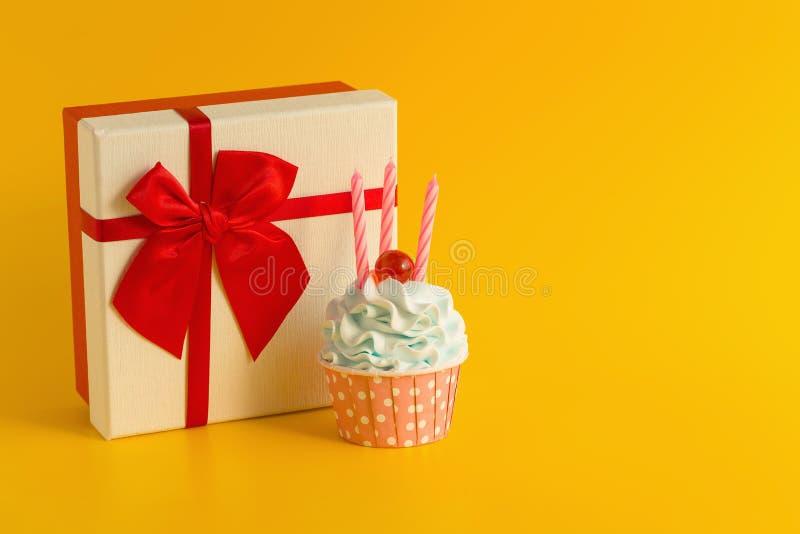鲜美生日杯形蛋糕和礼物盒在黄色颜色背景 免版税库存图片