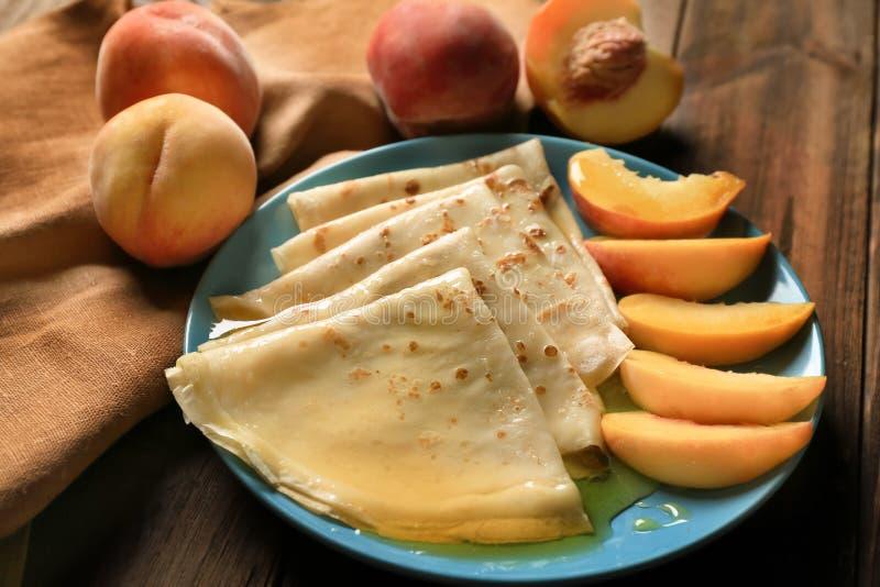 鲜美稀薄的薄煎饼板材用桃子 免版税库存照片
