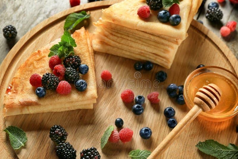 鲜美稀薄的薄煎饼用莓果在船上 免版税库存图片