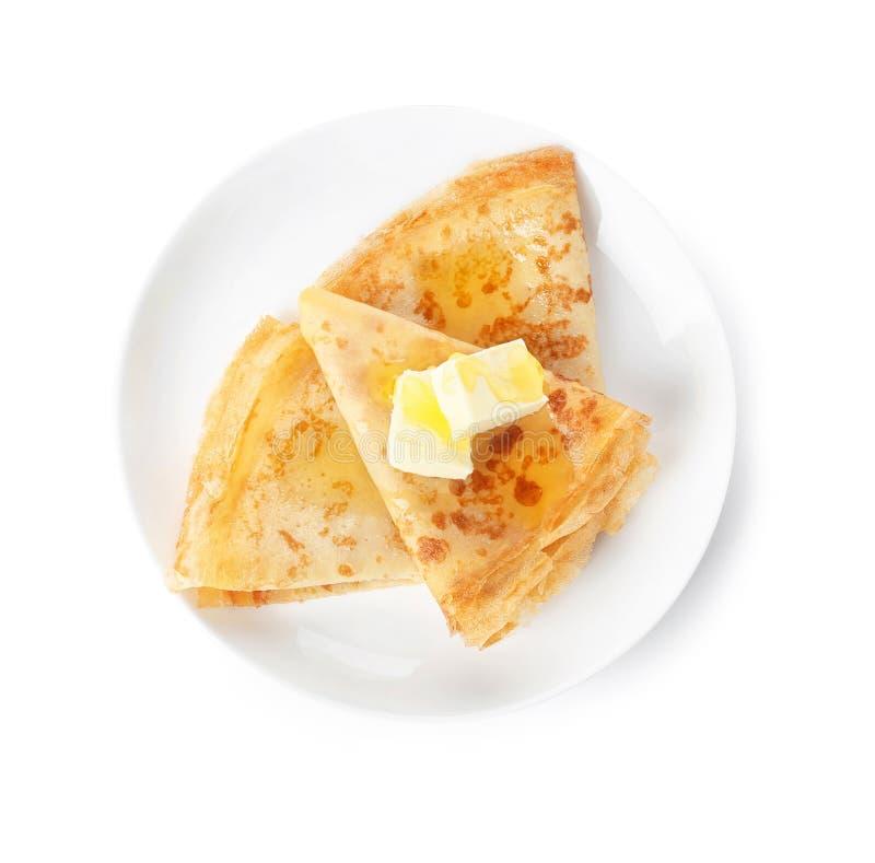 鲜美稀薄的被折叠的薄煎饼用黄油和蜂蜜在板材反对白色背景 免版税库存照片