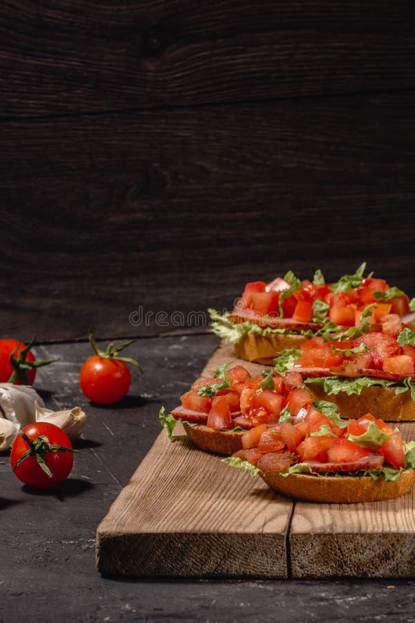 鲜美美味蕃茄意大利开胃菜或者bruschetta,在切片敬酒的长方形宝石装饰与沙拉叶子,火腿,砍了 免版税库存图片