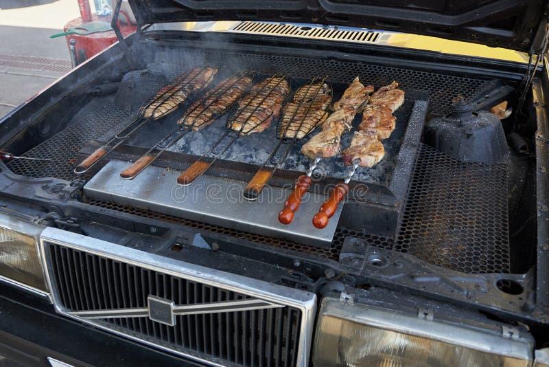 鲜美肉在格栅油煎,被做在一辆老富豪集团汽车的敞篷下 图库摄影