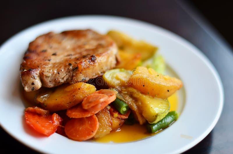 鲜美肉用土豆和菜在一个白色板材宏指令 免版税库存图片