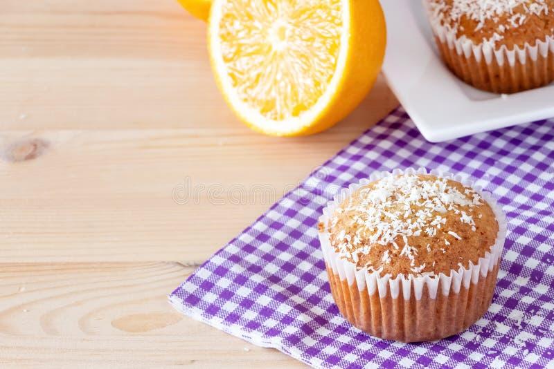 鲜美自创橙色松饼用椰子搽粉白色板材木背景 概念吃健康 选择聚焦 免版税库存照片