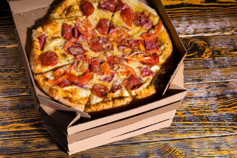 鲜美薄饼大角度看法用火腿,意大利辣味香肠,蕃茄和 免版税库存照片