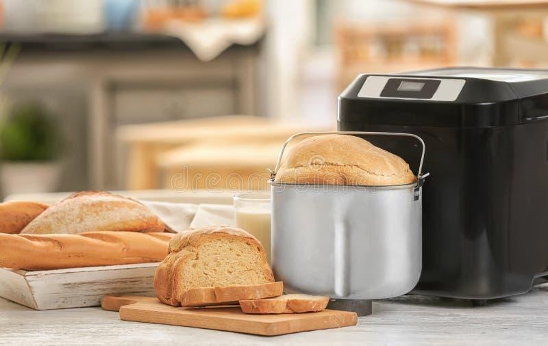 鲜美被切的大面包和面包机器 免版税库存照片