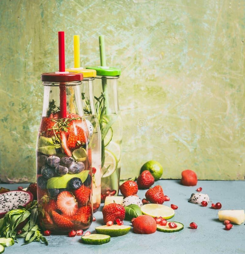 鲜美被灌输的水品种在瓶的有饮料秸杆和成份的,正面图 水调味用果子,莓果 免版税图库摄影