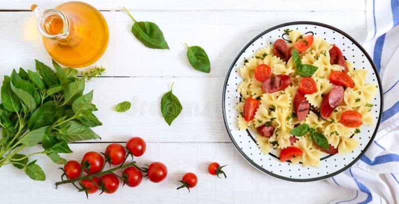 鲜美面团farfalle用烤香肠、新鲜的西红柿和蓬蒿在一块板材在白色木背景 r 免版税库存图片