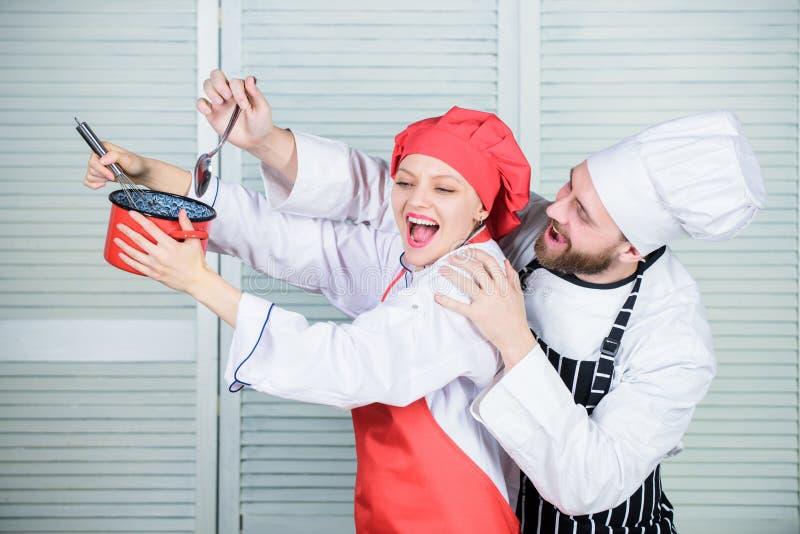 鲜美食物和好公司 由食谱的秘方 厨师制服 男人和妇女厨师在餐馆 耦合爱 免版税库存图片
