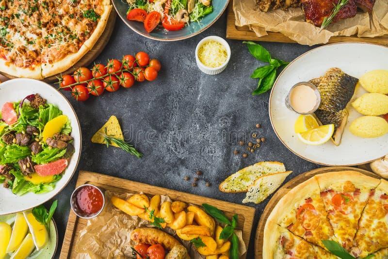 鲜美食物-烤猪排、薄饼、沙拉、鱼和香肠用油煎的土豆 平的位置 顶视图 库存照片